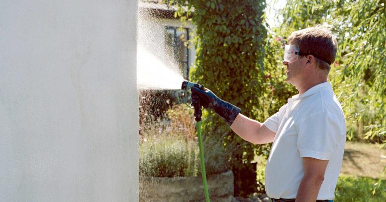 En mann spyler husveggen