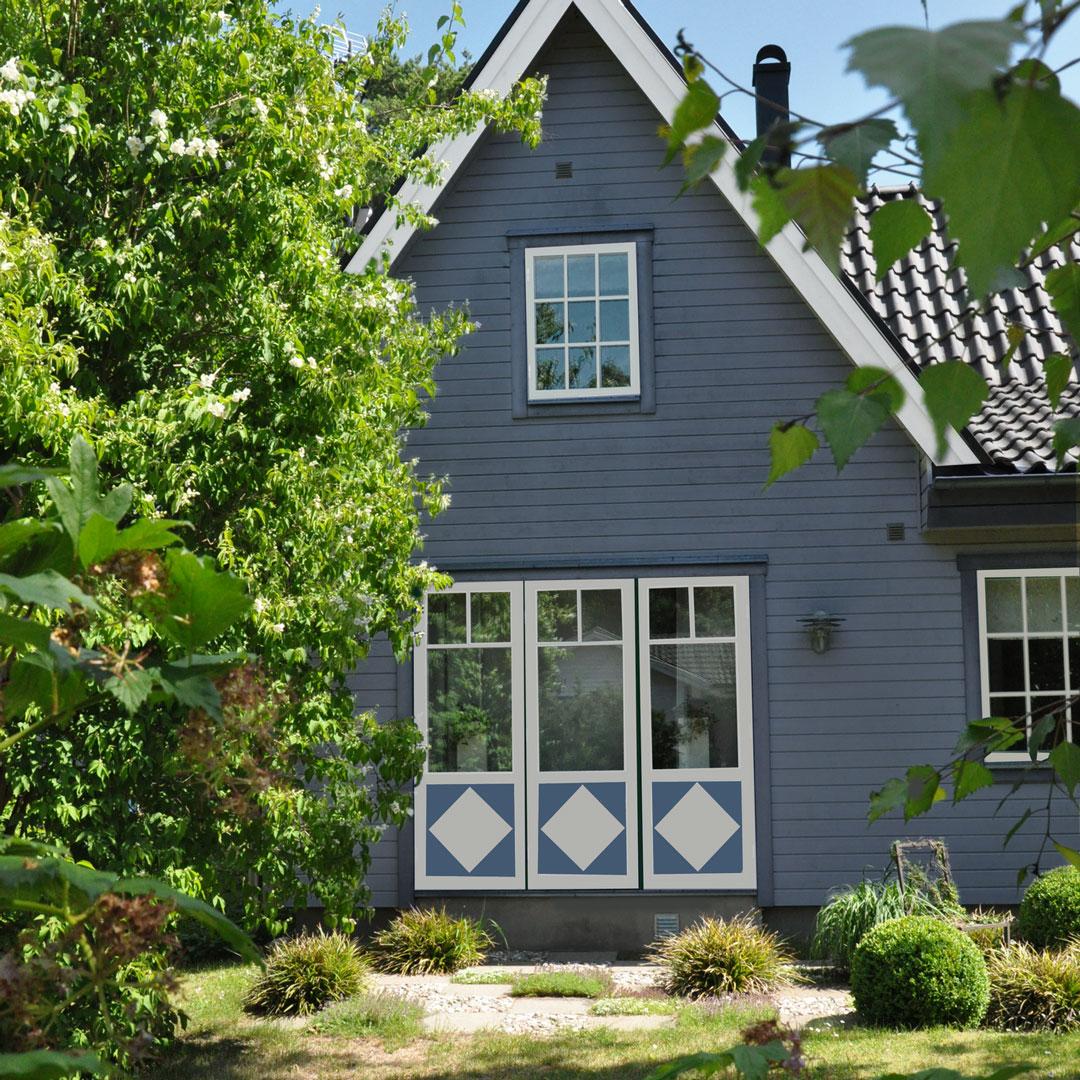 Nymalt blått hus med frodig og grønn hage