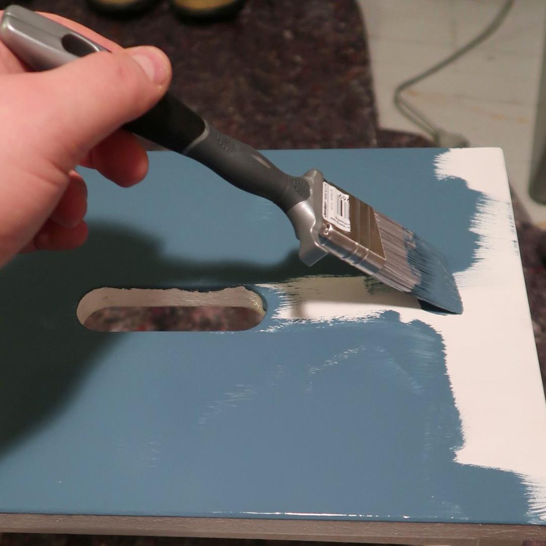 Nærbilde av en person som amler en hvit stol blå