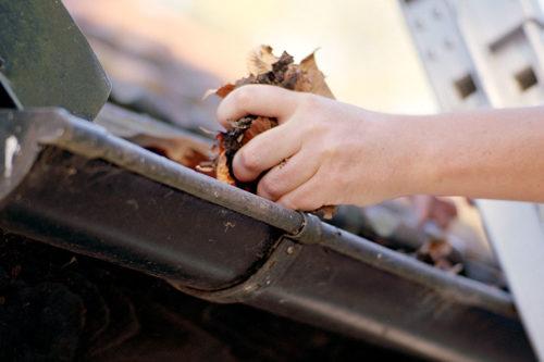nærbilde av en hpnd som renser takrennen før den skal males