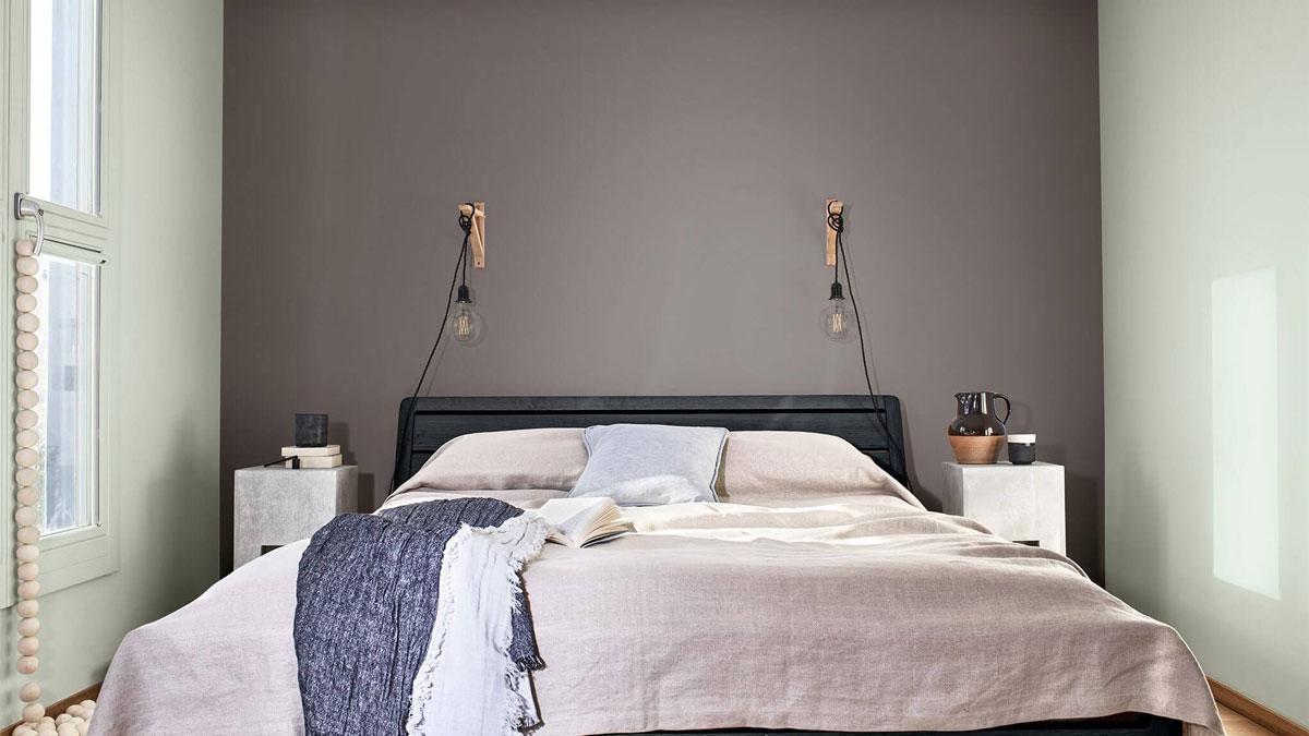 soverom med lyse grønne vegger og en grå vegg bak sengen