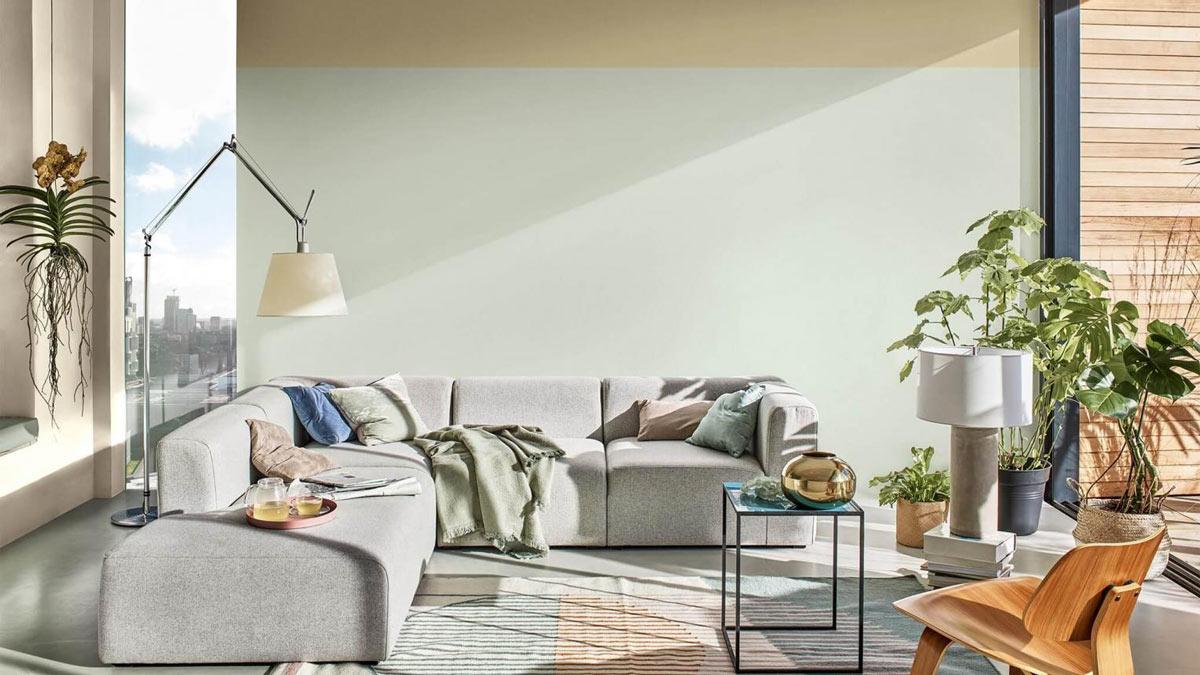 flott stue med lys grønn vegg bak og grå hjørnesofa i front